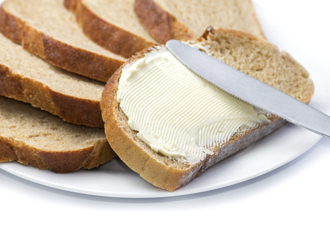 A knife spreading butter on bread.